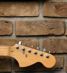 Gryf gitary na tle ściany.