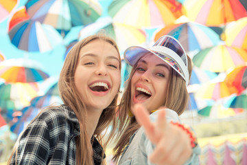 Happy young women walking outdoors with modern background of umb
