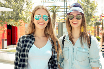 Lifestyle of two best friends in sunglasses laughing in city