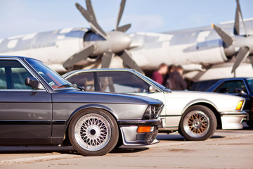 Right front side of two old european sport cars with plane on background