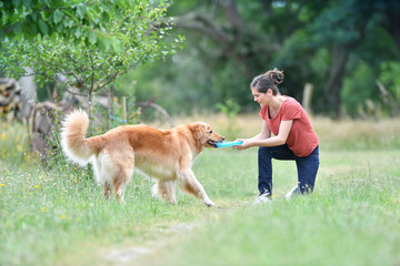 Woman playing with throwing frisbee to dog