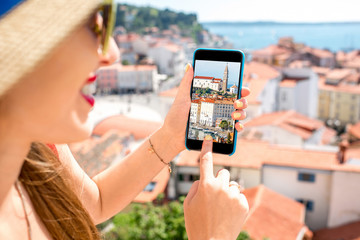 Young fwmale traveler photographing with smart phone Piran old town. Close up view focused on the phone screen