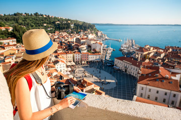 Young female traveler with red backpack and hat enjoying the view from George's tower on Piran old town. Traveling in Slovenia Fototapete
