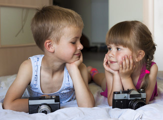 Children boy and girl brother and sister playing with cameras lo