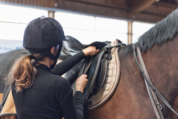Young female rider checking her stirrups