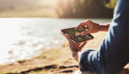 Male hands using digital tablet for navigation