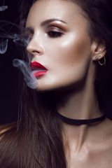 Beautiful sexy brunette girl with bright makeup, red lips, smoke from mouth. beauty face.