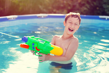 Happy little boy laugh and shoot with squirt gun