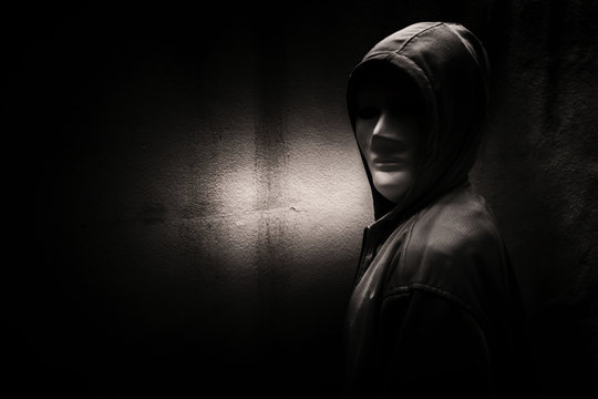 A stranger woman wearing hoodie with white mask hiding in the dark,Scary background for book cover