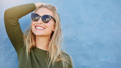 Stylish young woman in sunglasses smiling Wall mural
