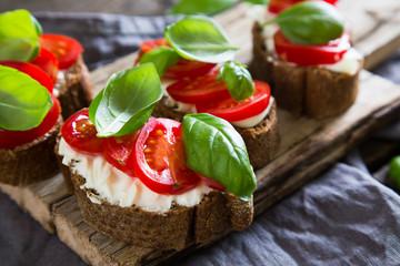 Bruschetta with cream cheese cherry tomatoes and basil