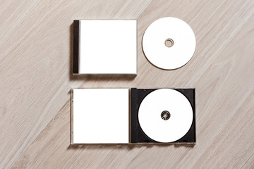 Closed compact disc template with plastic box case with white isolated blank for branding design and open box with booklet. CD jewel case mock up with clean free space for on wooden table. Top view