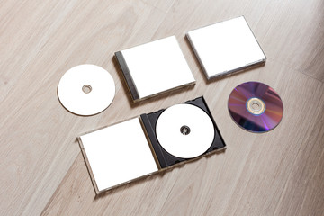 Full set compact disc template with plastic box case with white isolated blank for branding design and open box with booklet and back side. CD jewel case mock up with clean free space on wooden table.