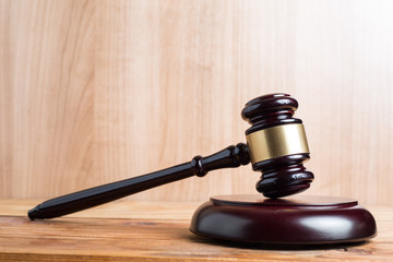 Wooden Judges gavel and golden scales justice with wooden background