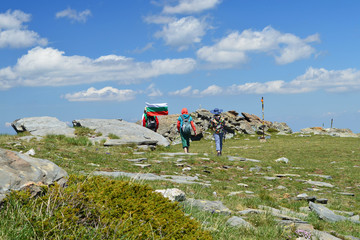 Two women hikers follow a man with Bulgarian national flag high in Rila Mountain. Sunny day, green alpine plateau and blue sky