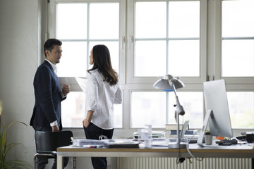 Businessman and woman standing at office window, disussing