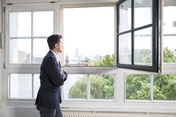 Businessman standing at open window with arms crossed