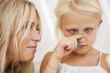 Cross-eyed little girl watching fly sitting on her finger
