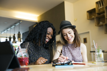 Two friends using digital tablet in cafe