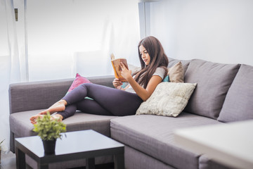 Teenage girl lying on the couch reading a book