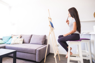 Teenage girl painting at home