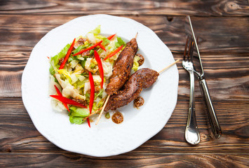 Hot teriyaki chicken with vegetables salad  on dark wooden backg