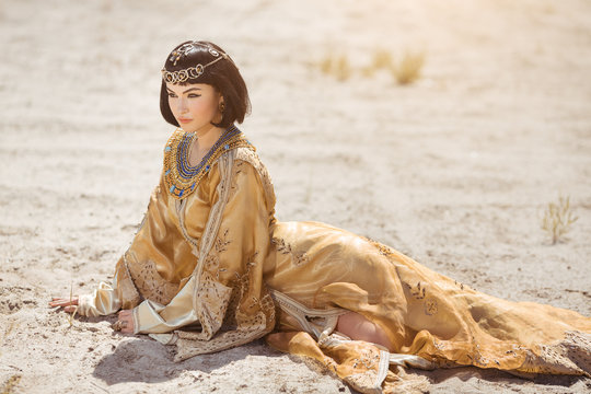 Beautiful woman like Egyptian Queen Cleopatra laying in desert outdoor.