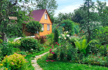 Summer wooden house on background of green garden,