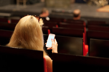 woman with a smartphone in an empty theater