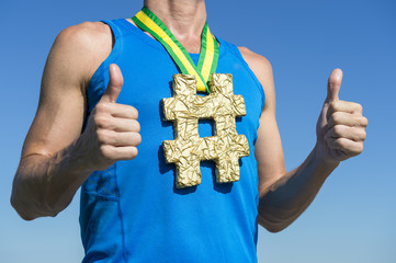 Athlete with hashtag gold medal hanging from Brazil colors green and yellow ribbon standing against bright blue sky