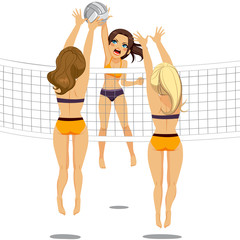 Active woman jumping doing smash attack while two athletic volleyball players are blocking ball