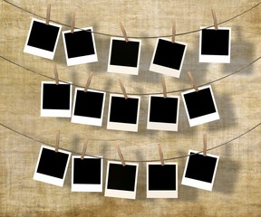 lots blank instant photos hanging on the clothesline