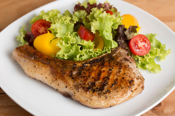 Grilled Pork serve with colorful salad on wooden table