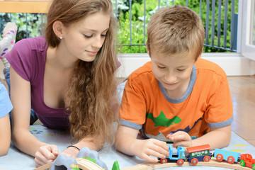 Mädchen als Babysitter spielt Holzeisenbahn mit Kind