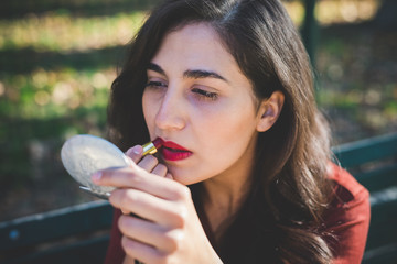 Young beautiful caucasian long brown hair woman outdoor in a city park putting lipstick on - beauty, make up concept