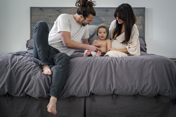 A young couple and their young son sitting together on their bed.