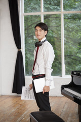 Young man standing next to a grand piano in a rehearsal studio, holding sheet music.