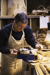 Man standing at a work bench in a carpentry workshop, working on a piece of wood secured in a bench vice.