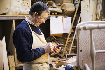 Man standing at a work bench in a carpentry workshop, working on a wooden chair.