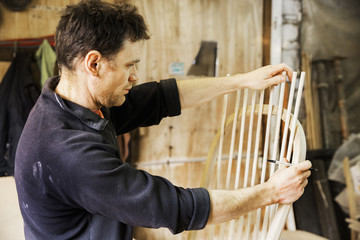 Man standing in a carpentry workshop, working on a wooden chair back.