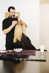 A hair colourist working with foils to give a client with long blonde hair highlights and lowlights using colour.