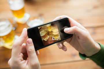 close up of hands with smartphone picturing beer