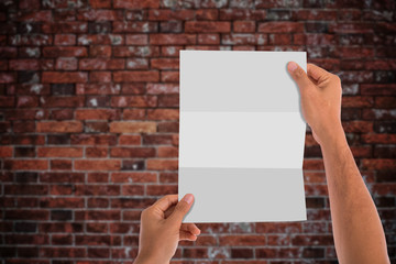 Hand Holding blank white paper or book with bricks background