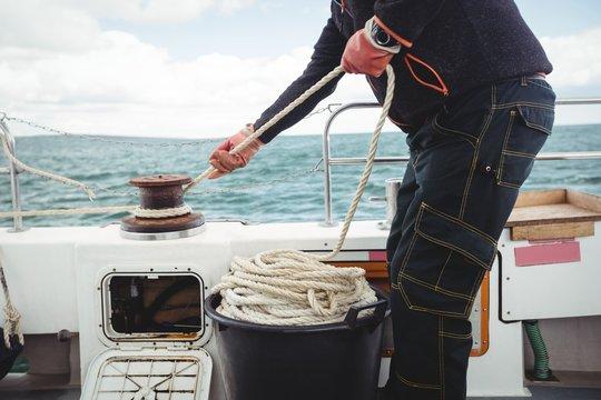 Fisherman tying rope on bollard