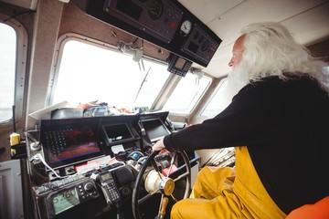 Fisherman driving fishing boat