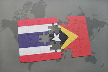 puzzle with the national flag of thailand and east timor on a world map background.