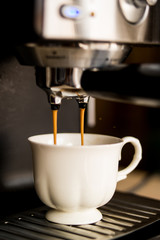 espresso machine making coffee and pouring in a white  cup