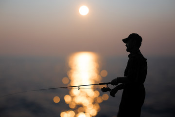 fisherman at dusk. silhouette of a fisherman with a fishing rod in the background reflected in water sunset.