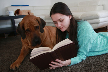 Young woman reading the book with dog