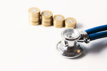 Stack of coins and stethoscope on white background.